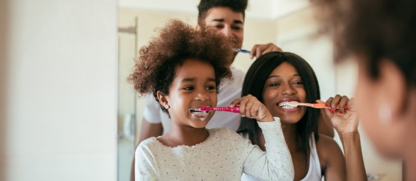 Family of three brushing teeth while looking in the bathroom mirror.