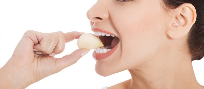 Woman eating natural garlic to get rid of toothache